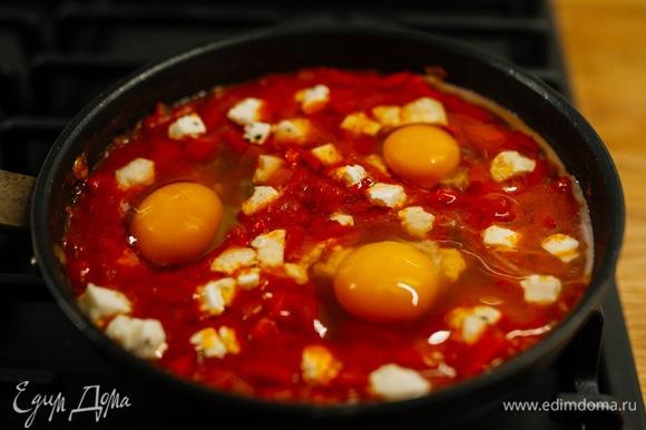 Сделать небольшие углубления и разбить туда яйца, слегка посолить.